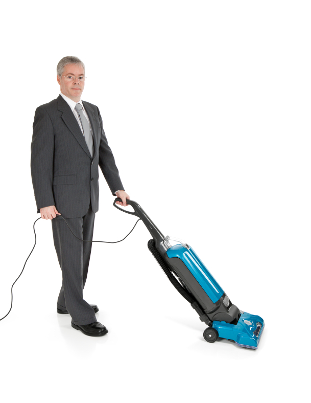 Man in a suit using a vacuum cleaner, isolated on white.